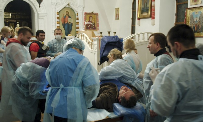 A man receives medical treatment inside Mikhailovsky Zlatoverkhy Cathedral in Kiev