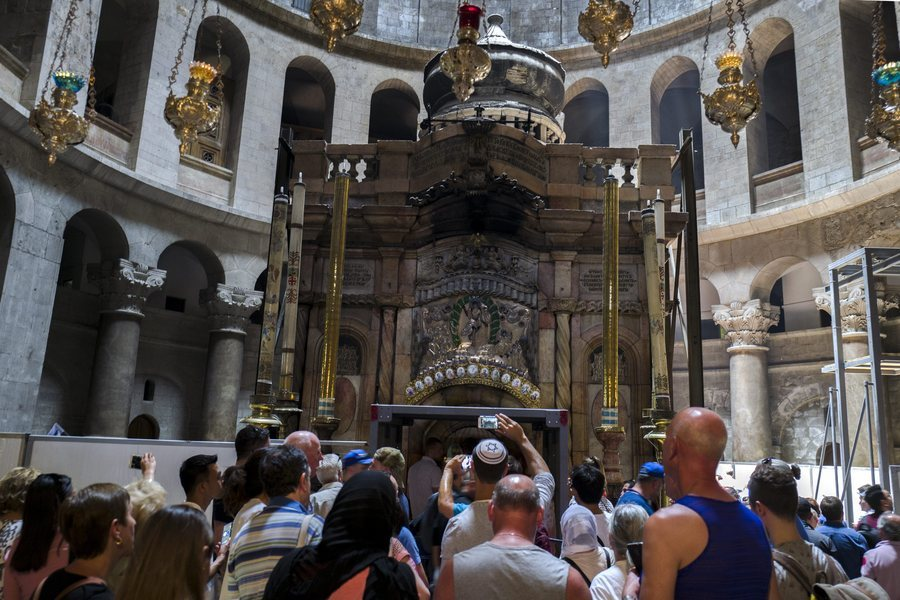 epa05342142 A group of Jewish Israelis visit the rotunda in the Church of the Holy Sepulchre in Jerusalem's Old City as a man with a Star of David 'yamulka', or skullcap, takes a photograph of the entrance to the Tomb of Jesus Christ, 02 June 2016. A metal cage-like structure has been built at the entrance and white fencing placed around the tomb as renovation work begins to salvage the tomb from further damage. Restoration work on the Tomb of Christ is expected to take up to a year and pilgrims and tourists will be able to continue to visit the holy site where tradition holds Jesus Christ was buried and resurrected. The construction work is the first at the site for almost 200 years and will focus on reinforcing the structure.  EPA/JIM HOLLANDER