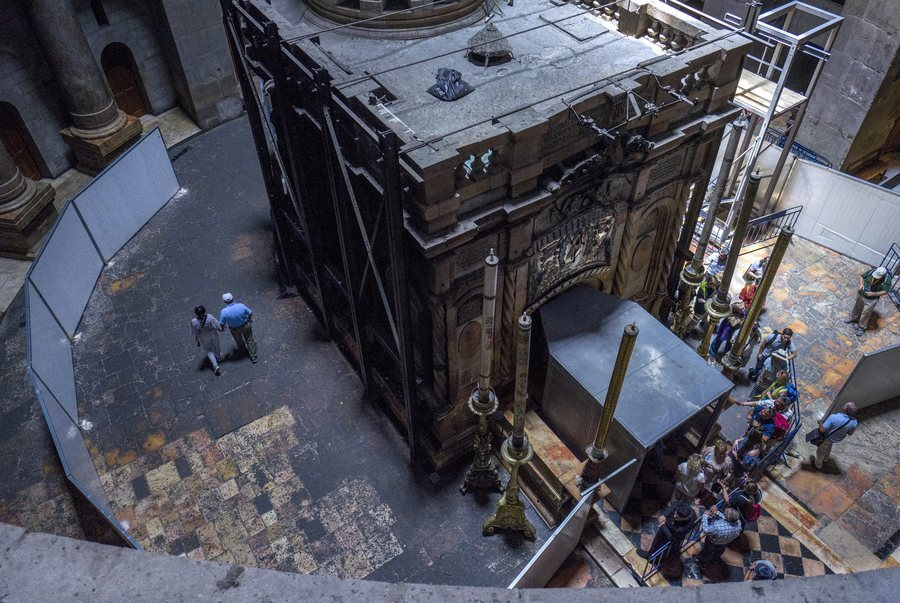 epa05342144 Tourists walk between fencing an Tomb of Jesus Christ (R) in the rotunda inside the Church of the Holy Sepulchre in Jerusalem's Old City were pilgrims line up to visit Christ's tomb (R) as renovation work on the historic religious site is in progress, 02 June 2016. A large metal cage-like structure (R bottom) is placed at the tomb's entrance to keep anything from falling on visitors. Restoration work on the Tomb of Christ is expected to take up to a year and pilgrims and tourists will be able to continue to visit the holy site where tradition holds Jesus Christ was buried and resurrected. The construction work is the first at the site for almost 200 years and will focus on reinforcing the structure and preventing further decay and damage.  EPA/JIM HOLLANDER