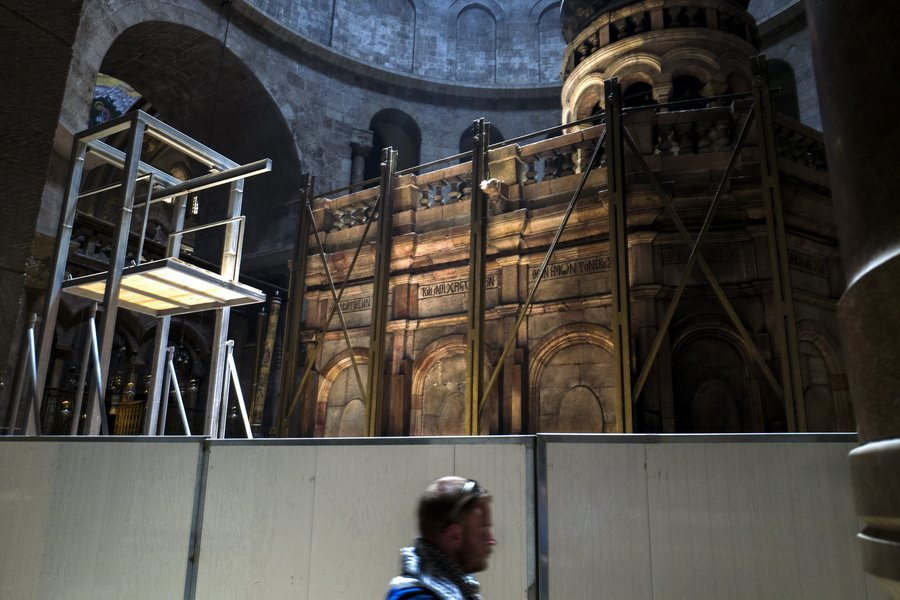 epa05342143 A tourists walks past a fence in the rotunda of the Church of the Holy Sepulchre in Jerusalem's Old City to divide large round room where the Tomb of Jesus Christ (rear) is undergoing renovation work, 02 June 2016.A large metal scaffolding (L) is also placed near the tomb. Restoration work on the Tomb of Christ is expected to take up to a year and pilgrims and tourists will be able to continue to visit the holy site where tradition holds Jesus Christ was buried and resurrected. The construction work is the first at the site for almost 200 years and will focus on reinforcing the structure and preventing further decay and damage.  EPA/JIM HOLLANDER