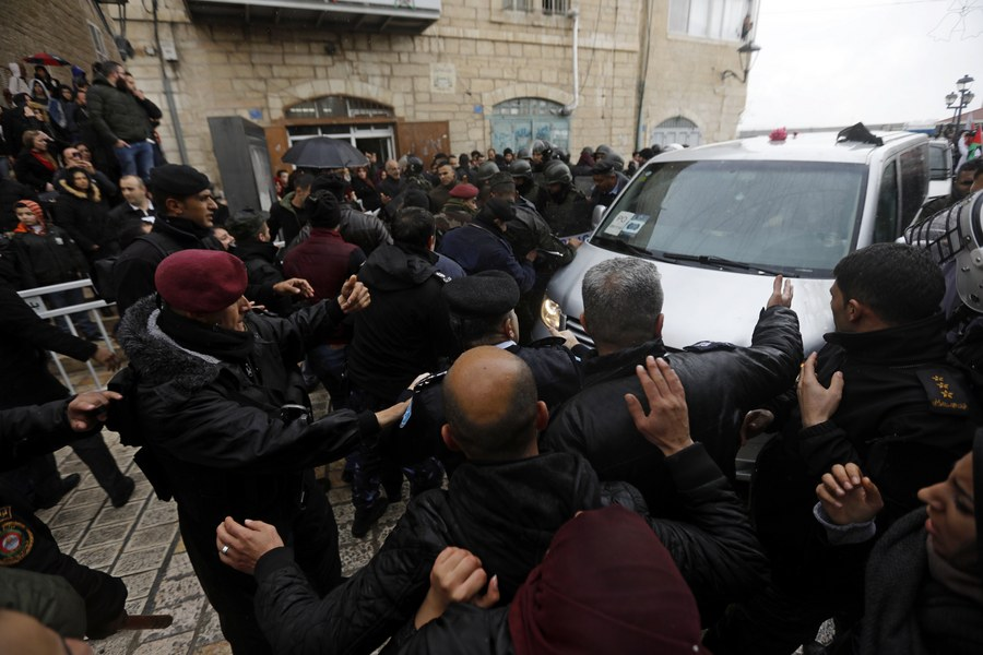 epa06419922 Palestinian security forces push away demonstrators from the convoy of Greek Orthodox Patriarch of Jerusalem Theophilos III, during a protest against his visit in the West Bank city of Bethlehem, 06 January 2018. EPA/ABED AL HASHLAMOUN