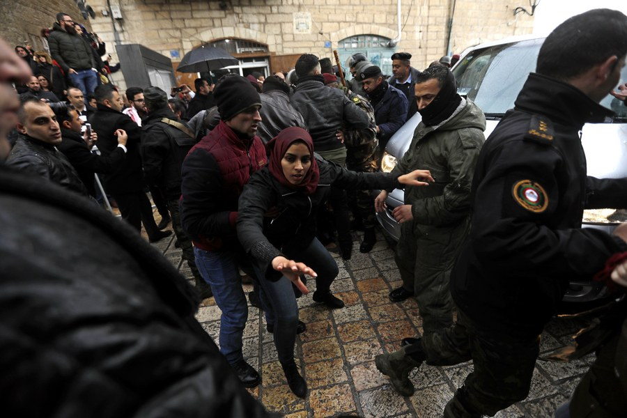 epa06419925 Palestinian security forces push away demonstrators from the convoy of Greek Orthodox Patriarch of Jerusalem Theophilos III, during a protest against his visit in the West Bank city of Bethlehem, 06 January 2018. EPA/ABED AL HASHLAMOUN