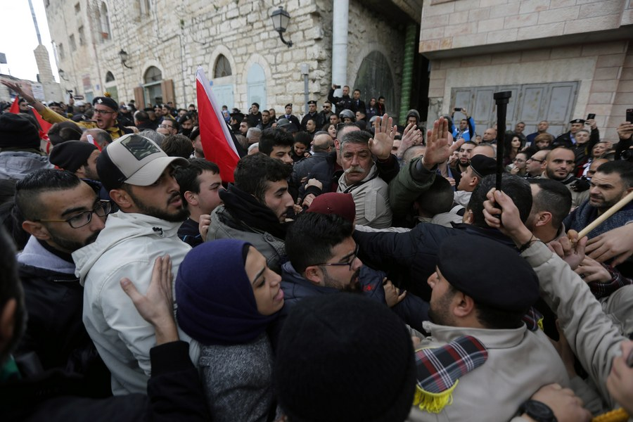 epa06419926 Palestinian security forces push away demonstrators from the convoy of Greek Orthodox Patriarch of Jerusalem Theophilos III, during a protest against his visit in the West Bank city of Bethlehem, 06 January 2018. EPA/ABED AL HASHLAMOUN