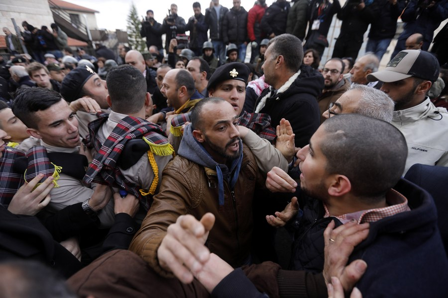 epa06419924 Palestinian security forces push away demonstrators from the convoy of Greek Orthodox Patriarch of Jerusalem Theophilos III, during a protest against his visit in the West Bank city of Bethlehem, 06 January 2018. EPA/ABED AL HASHLAMOUN