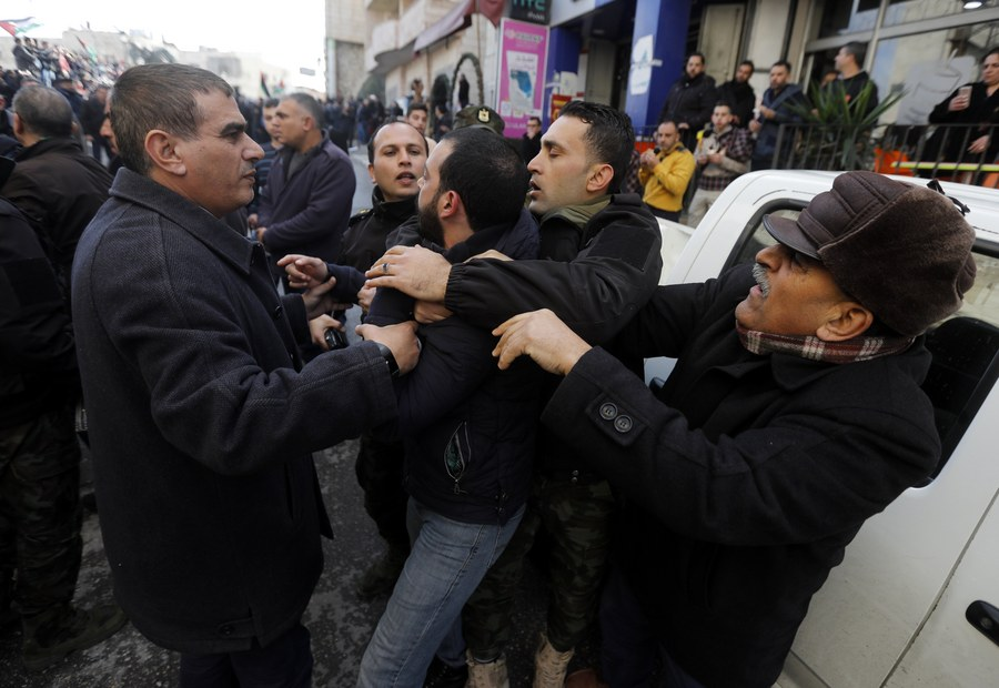 epa06419974 Palestinian security forces push away demonstrators from the convoy of Greek Orthodox Patriarch of Jerusalem Theophilos III, during a protest against his visit in the West Bank city of Bethlehem, 06 January 2018. The protest are against the Church's alleged sale of church lands to Israelis. EPA/ABED AL HASHLAMOUN